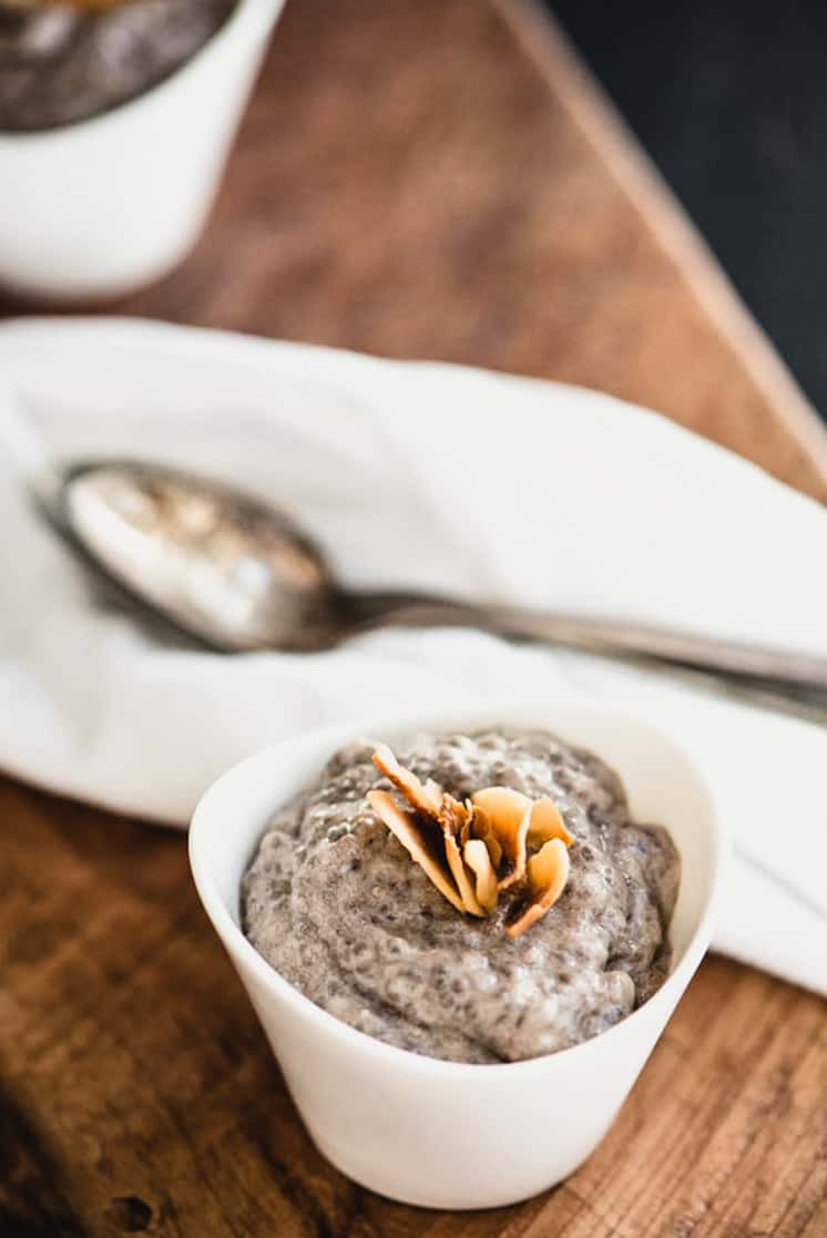 close up of banana chia seed pudding with toasted coconut and a spoon