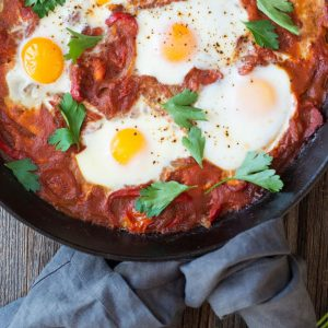 Make this one-skillet Shakshuka recipe for your next weekend breakfast. Eggs are gently nestled in a lightly spiced tomato sauce and baked! | StupidEasyPaleo.com