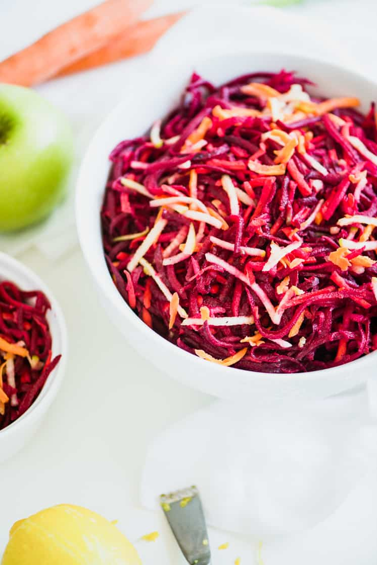 red and orange shredded beets and carrots in a white bowl
