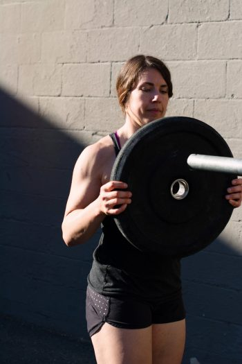 woman with brown hair puts weight plate onto the end of a barbell