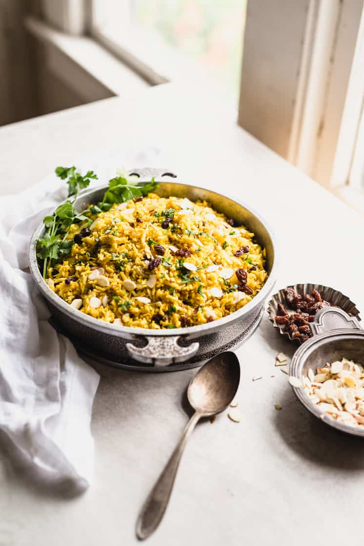 table shot of cauliflower rice with curry powder, raisins, and almonds