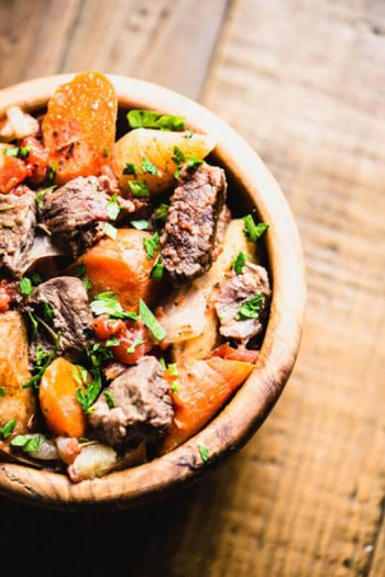 beef stew with hearty vegetables in a wooden bowl
