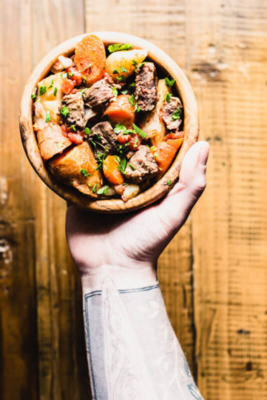 beef stew with veggies in a wooden bowl