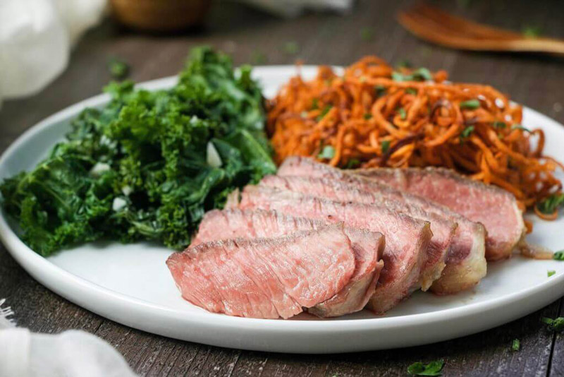 Paleo Reverse Seared Steak Dinner is so simple and ticks all the boxes with juicy steak, crispy sweet potatoes fries, and garlicky kale. | StupidEasyPaleo.com