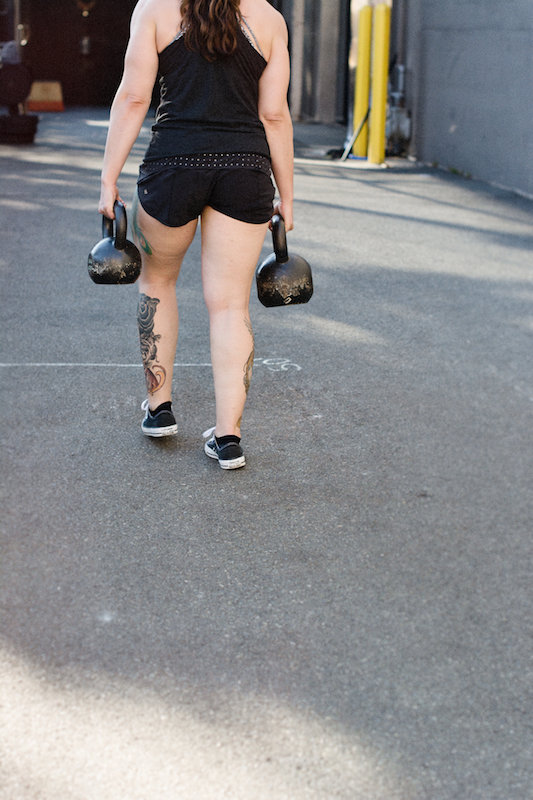 Woman holding kettlebells and doing a farmers carry for the Made Strong program