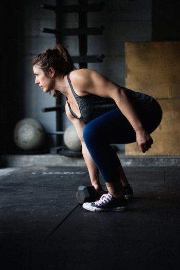Woman holding dumbbell about to do a dumbbell snatch for the Made Strong program