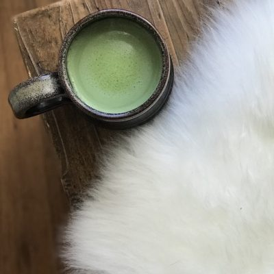 Matcha green tea on a bench with a sheepskin.