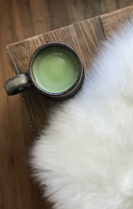 Matcha green tea on a bench with a sheepskin.