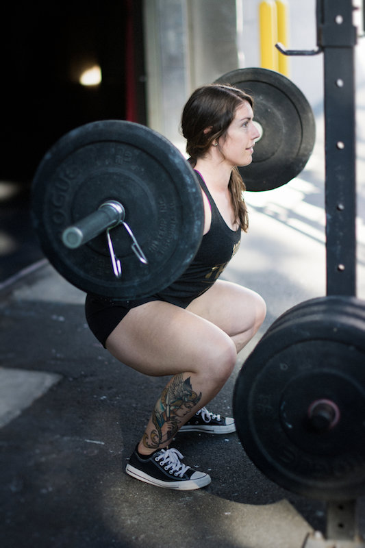 Steph with a barbell doing a back squat