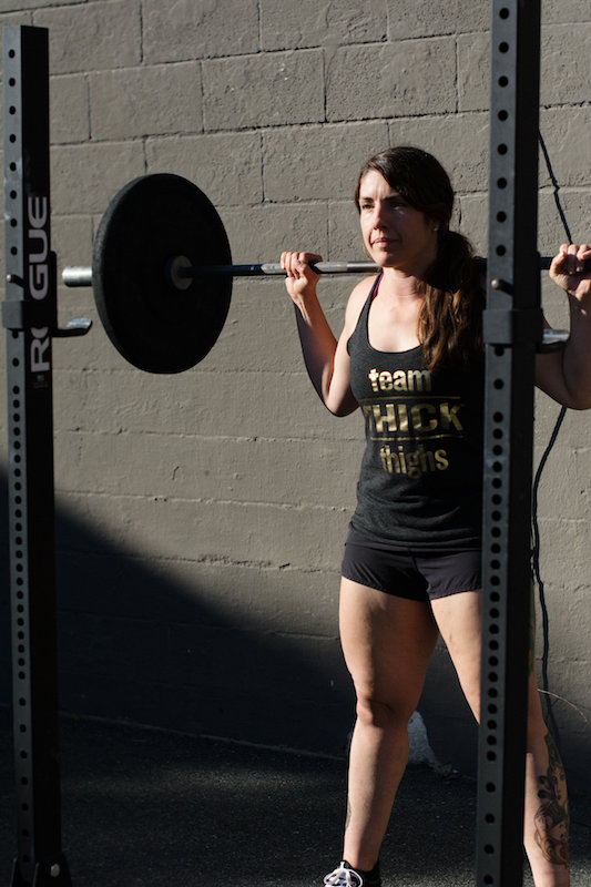 Steph, brown haired white woman, with a barbell doing a back squat