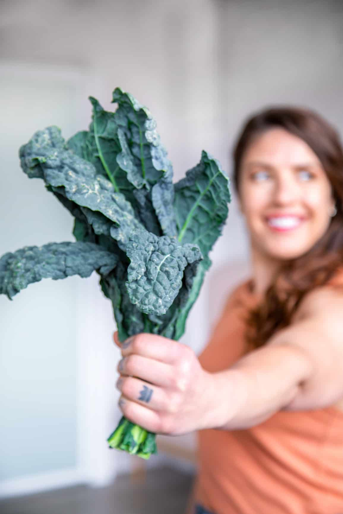 white woman with long brown wavy hair in orange tank top holds a bunch of kale to the camera