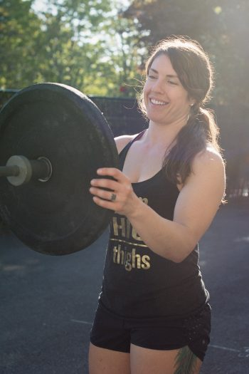 white woman with long brown wavy hair in black tank top puts a large plate onto the end of a barbell