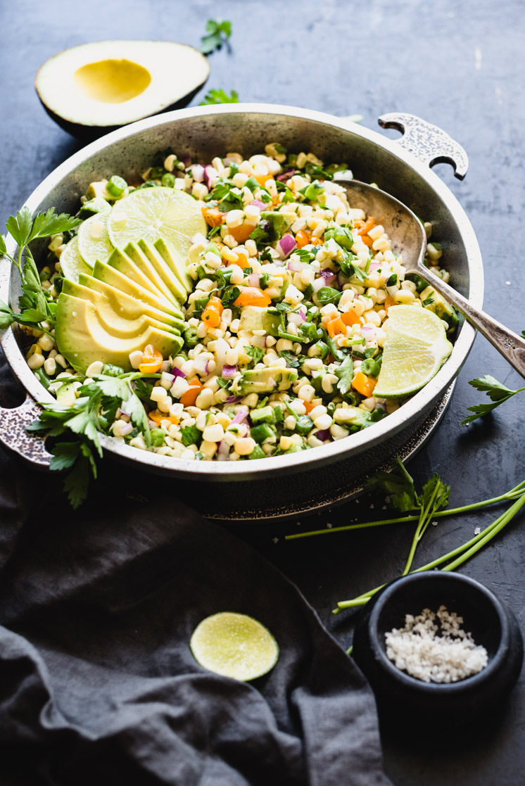 Fresh Corn Salad with Avocado for your summer table? Heck yes! Crunchy sweet corn, savory tomatoes, earthy green beans, creamy avocado, and zesty lime get friendly in this raw salad perfect for hot weather. It's gluten-free, plant-based, and comes together in just minutes! | StupidEasyPaleo.com