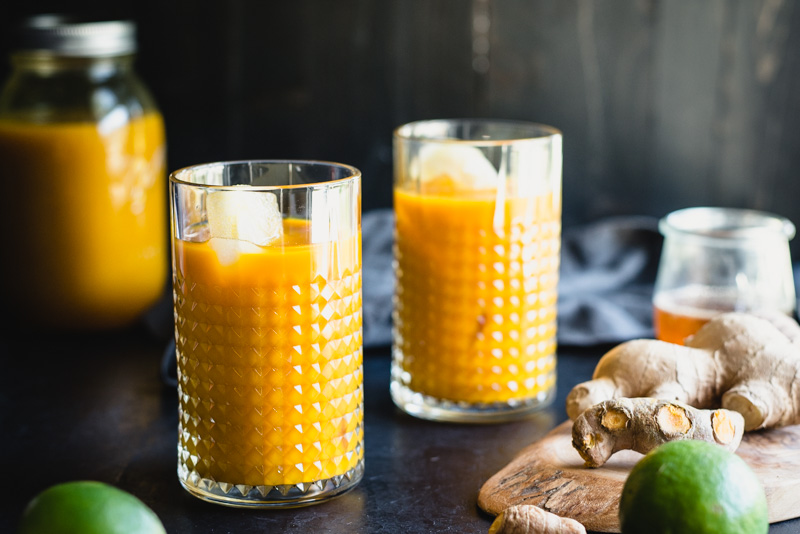 two glasses of orange turmeric root tonic with ginger and lime