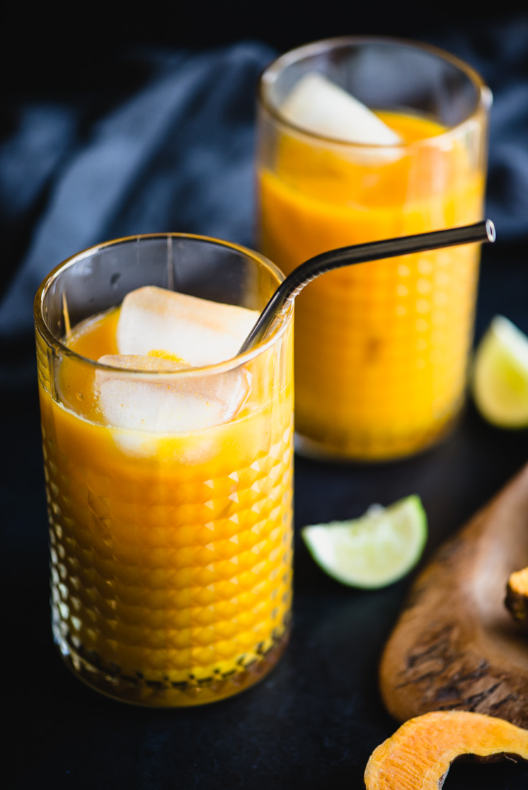 healing turmeric root tonic in a glass with ice cubes and a metal straw