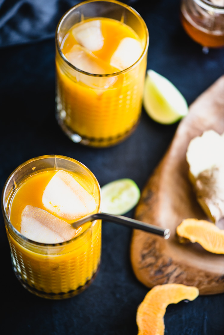 close up of bright orange turmeric tonic in two glasses with ice