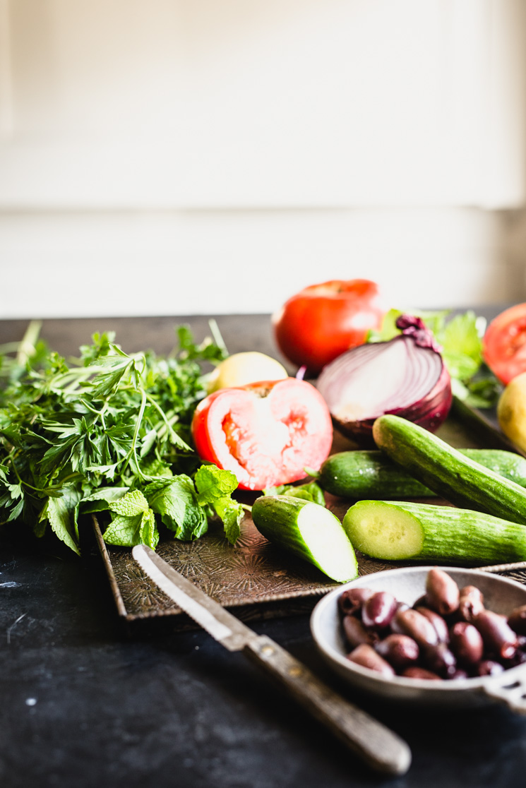 ingredients for simple greek salad with cucumber, tomato, red onion, and herbs