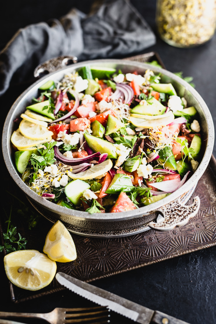 healthy greek salad packed with vegetables in a metal bowl