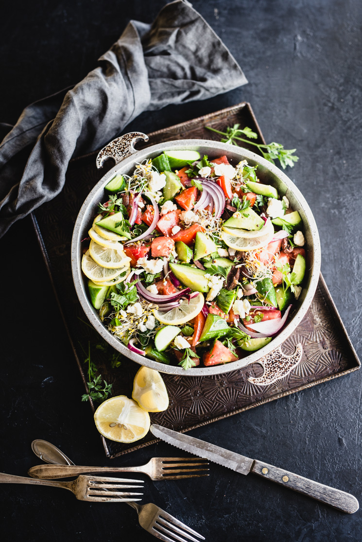simple greek salad with colorful veggies in a bowl on a metal tray