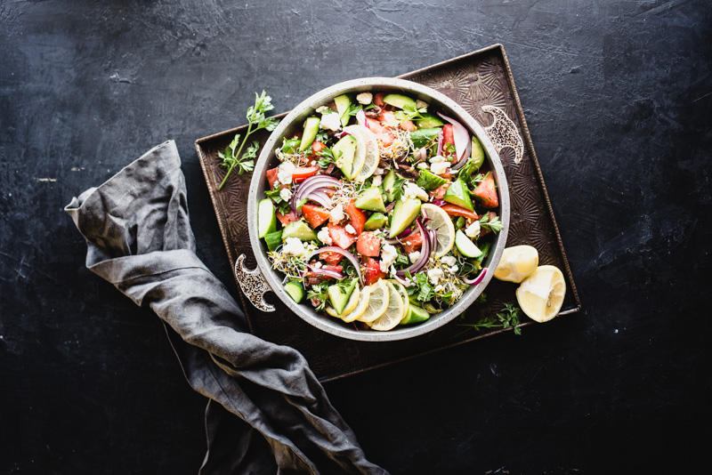 overhead shot of simple greek salad with healthy vegetables on a dark background