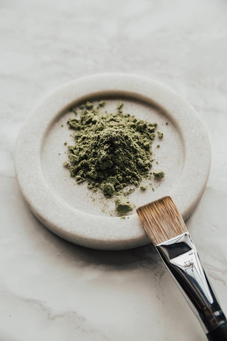 Natural makeup green powder with a makeup brush on a circular piece of white marble.