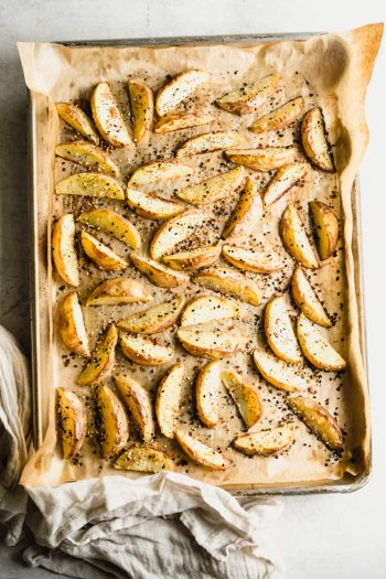 tray of crispy golden brown roasted potato wedges with everything seasoning