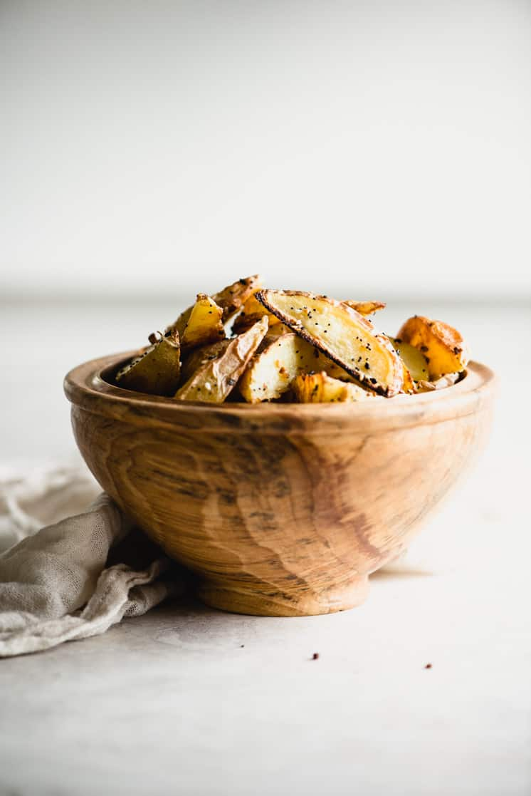 roasted potato wedges piled high in a wooden bowl