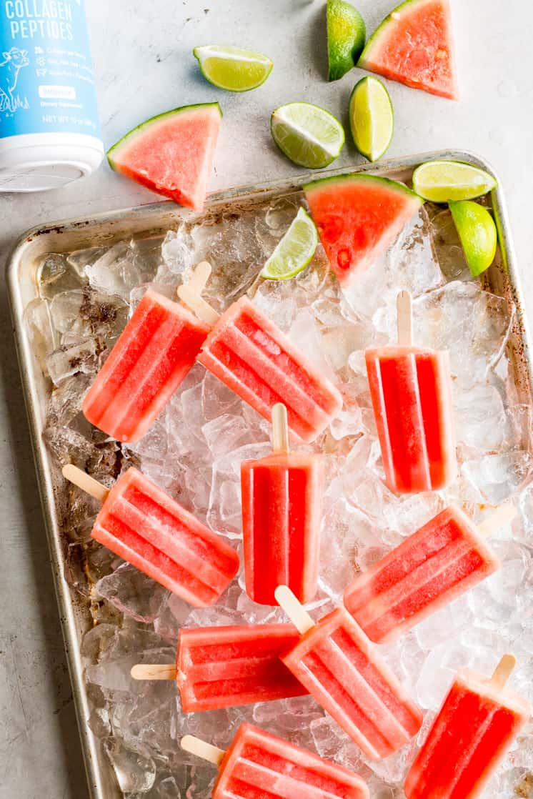 overhead photo of a tray of watermelon popsicles with collagen container