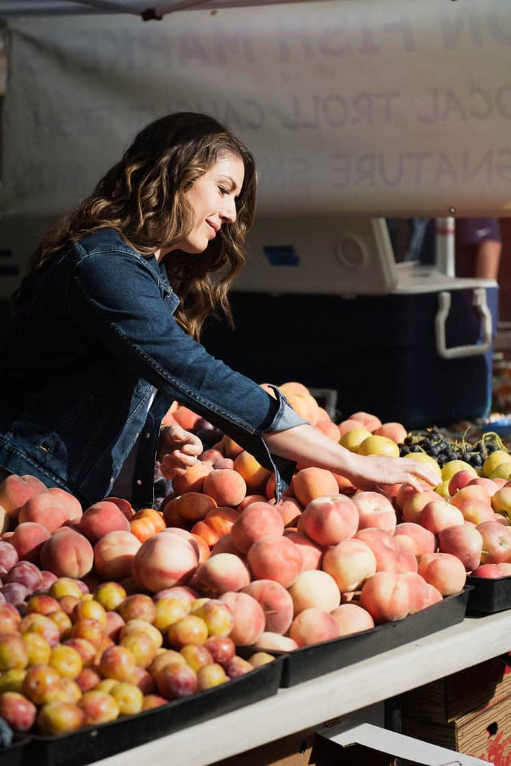 woman with brown hair shopping for fruit at a farmers market