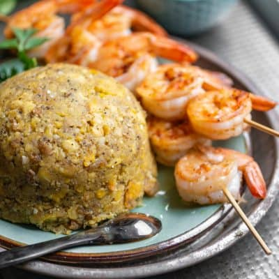 puerto rican mofongo (mashed plantains) served with grilled shrimp skewers