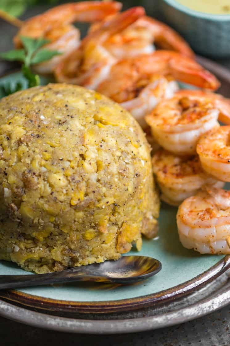 mofongo a mashed plantain dish on a blue plate with grilled shrimp