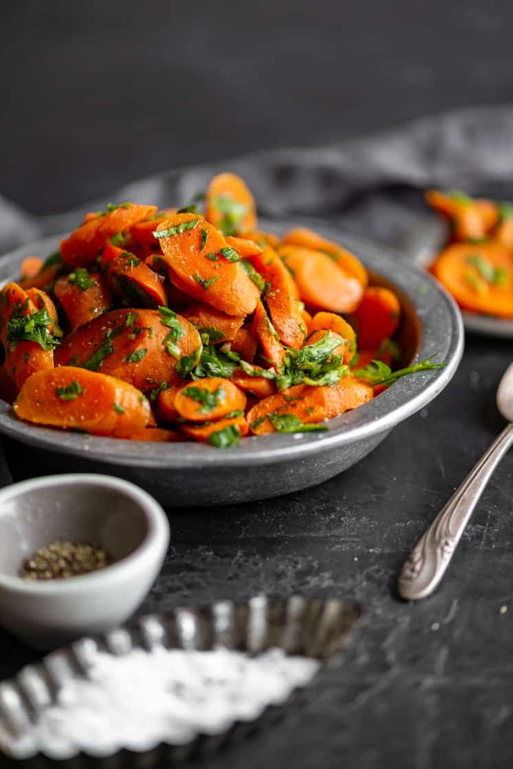 bright orange carrots and green parsley heaped up in a bowl