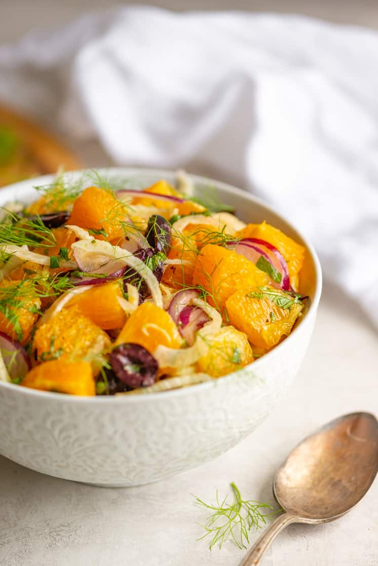 oranges red onion mint and olives in a white bowl