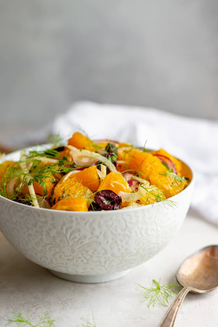 colorful salad with oranges in a white bowl with a metal spoon