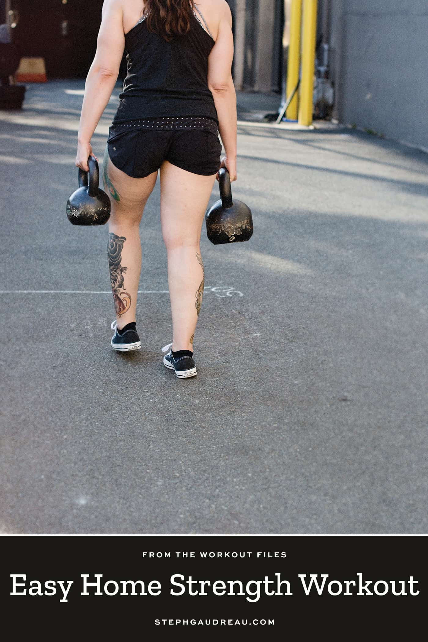 woman walking holding a kettlebell in each hand