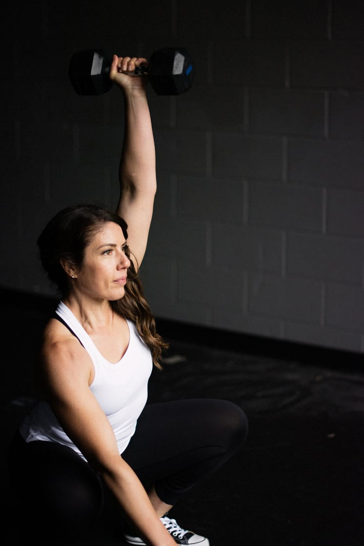 woman in white tank top and black pants squatting holding dumbbell overhead