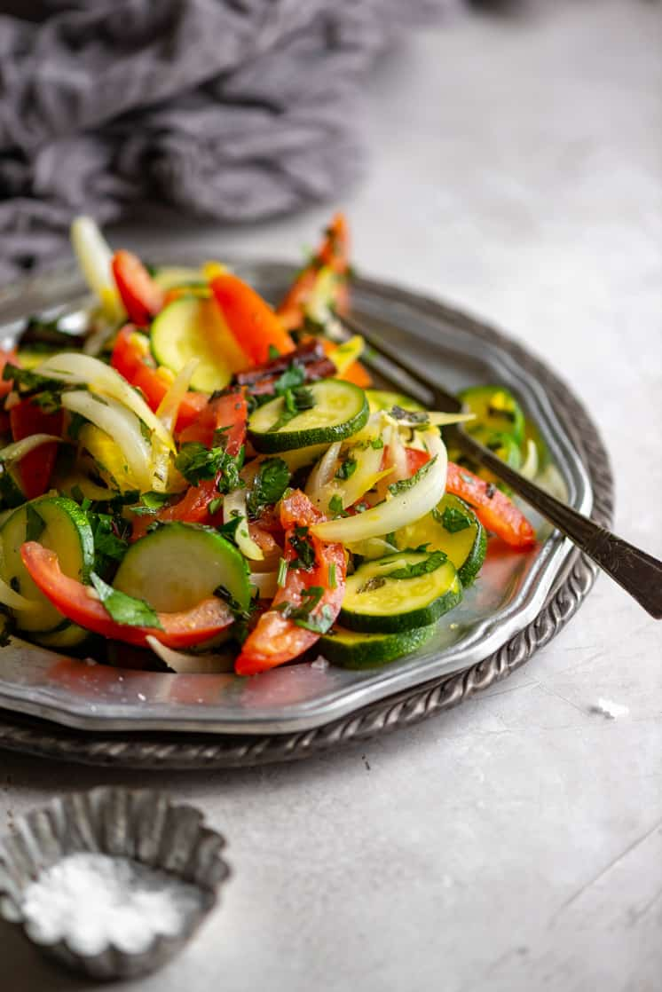 zucchini and tomato salad on a silver plate