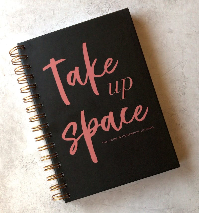 black journal cover that says take up space in pink