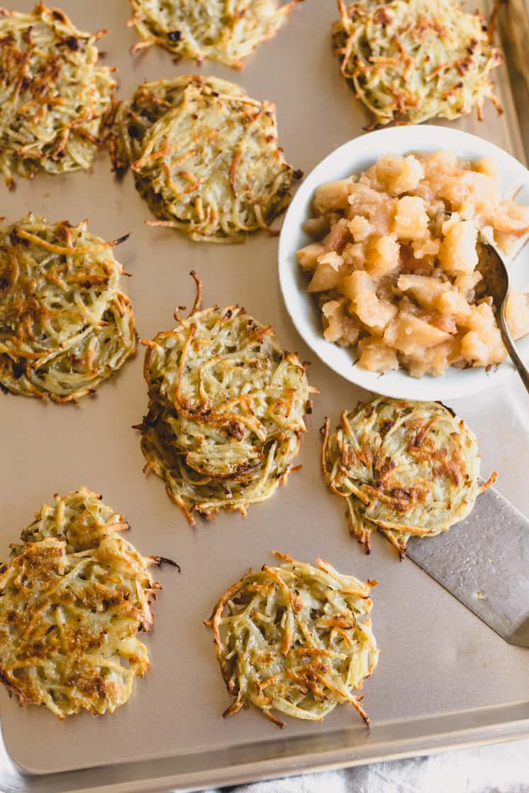potato latkes on a baking tray with applesauce