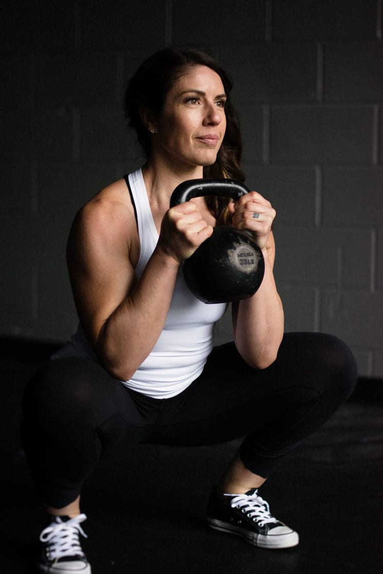 woman with brown hair squatting holding kettlebell at chest level