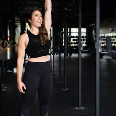 woman with brown hair holding a kettlebell overhead with one arm