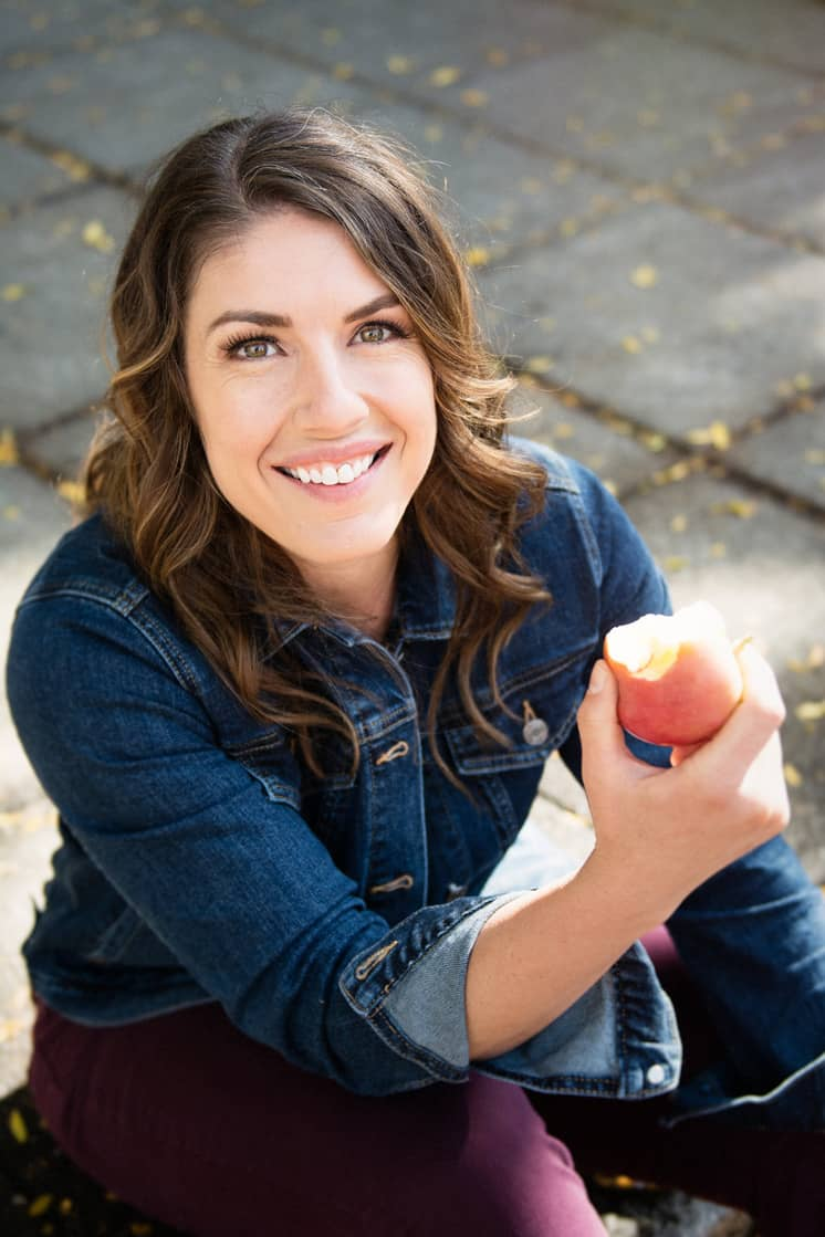 woman with brown hair holding an apple