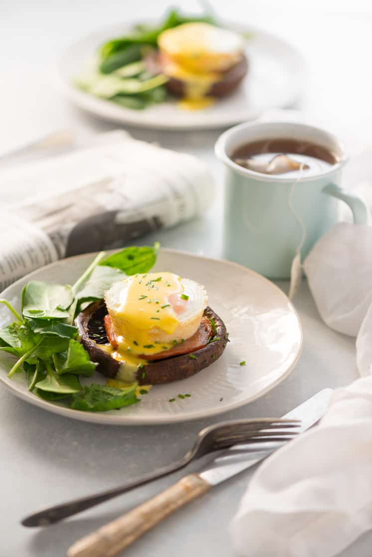 eggs benedict on a white plate with a mug of tea