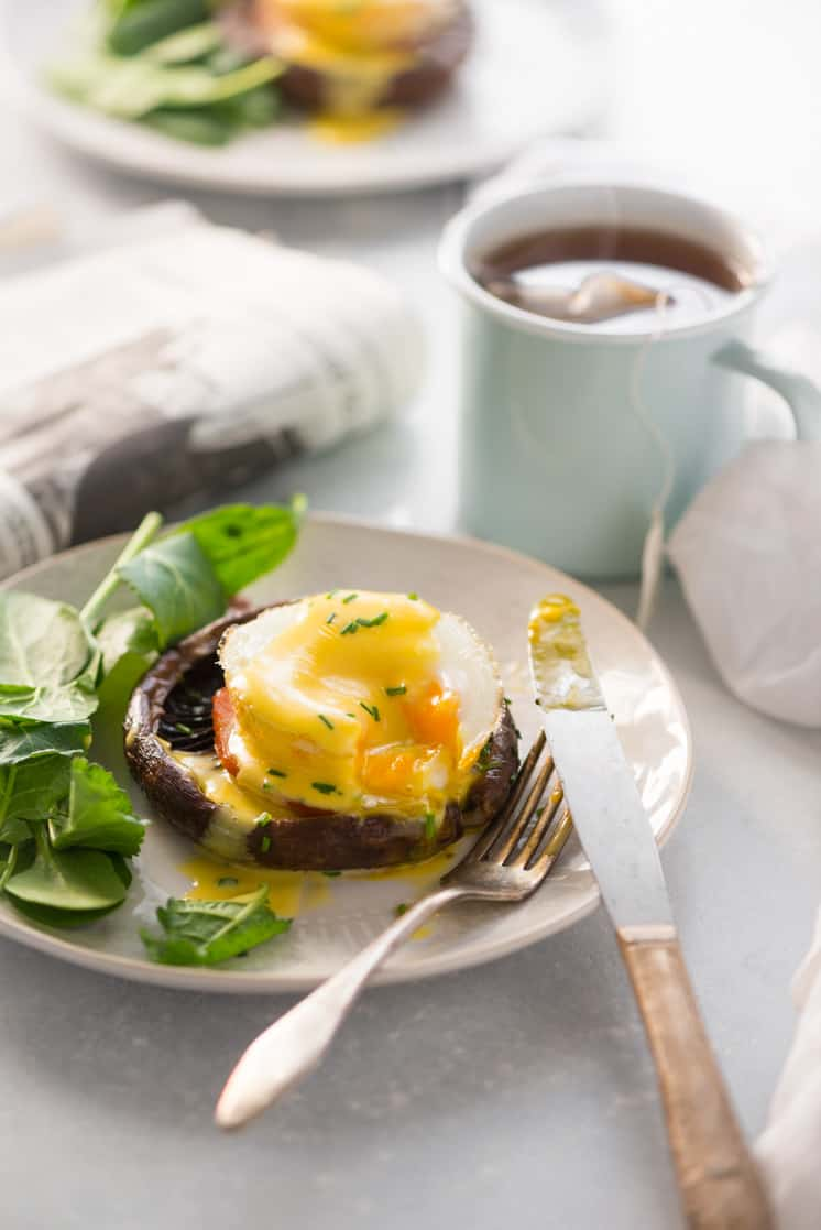 eggs benedict on a white plate with a newspaper and breakfast scene on the table