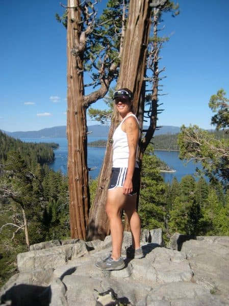 white woman wearing baseball cap, white tank top, and shorts standing in a forest next to a lake