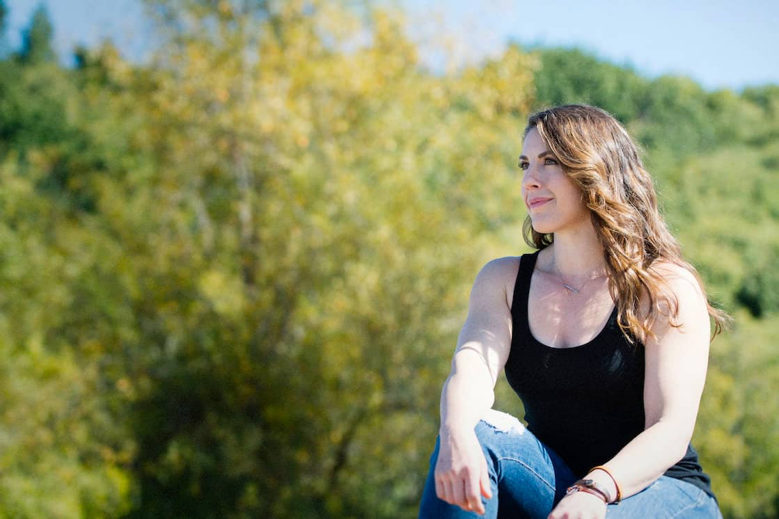 white woman with long brown wavy hair wearing black tank top and jeans sitting in front of trees