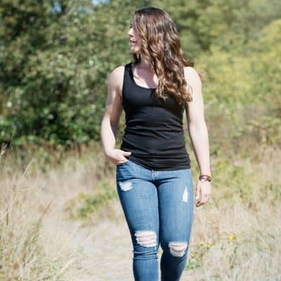 white woman with long brown hair black tank top ripped jeans walking on a path