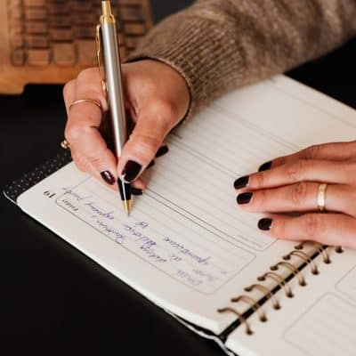 closeup of hands writing in a journal