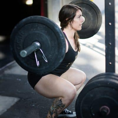 white woman with long brown hair squatting with a barbell on her back