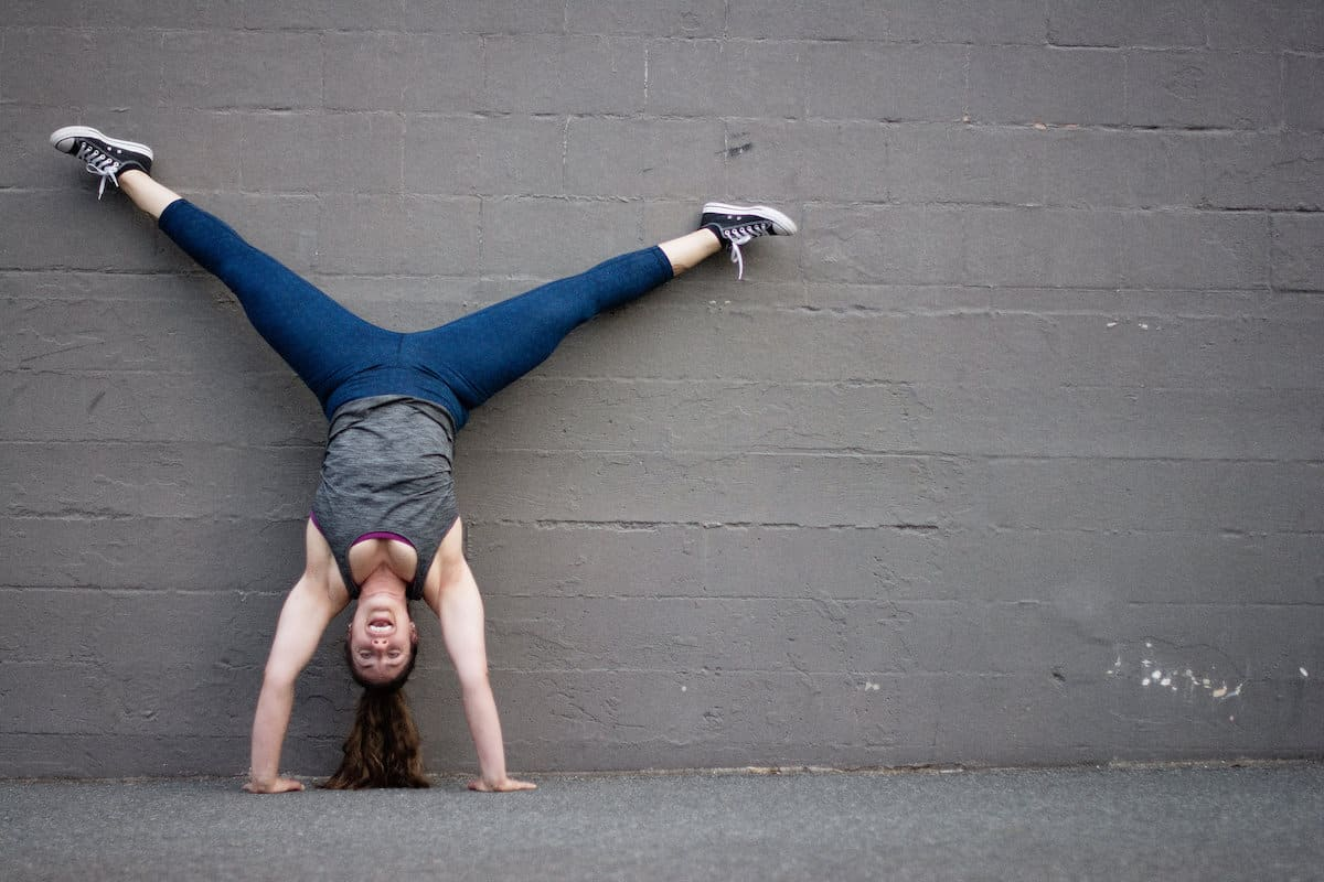 white woman with long brown hair doing a handstand against a grey wayll